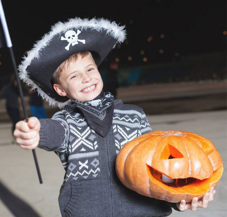Halloween Skate - Boy dressed as a pirate holding a jack-o-lantern