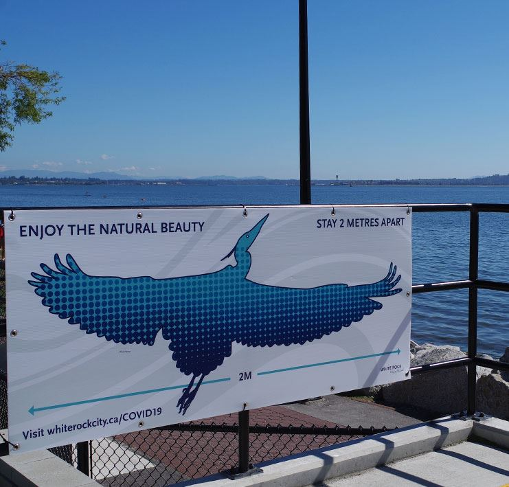 Blue heron sign at White Rock Waterfront reminding visitors to stay 2 metres apart.