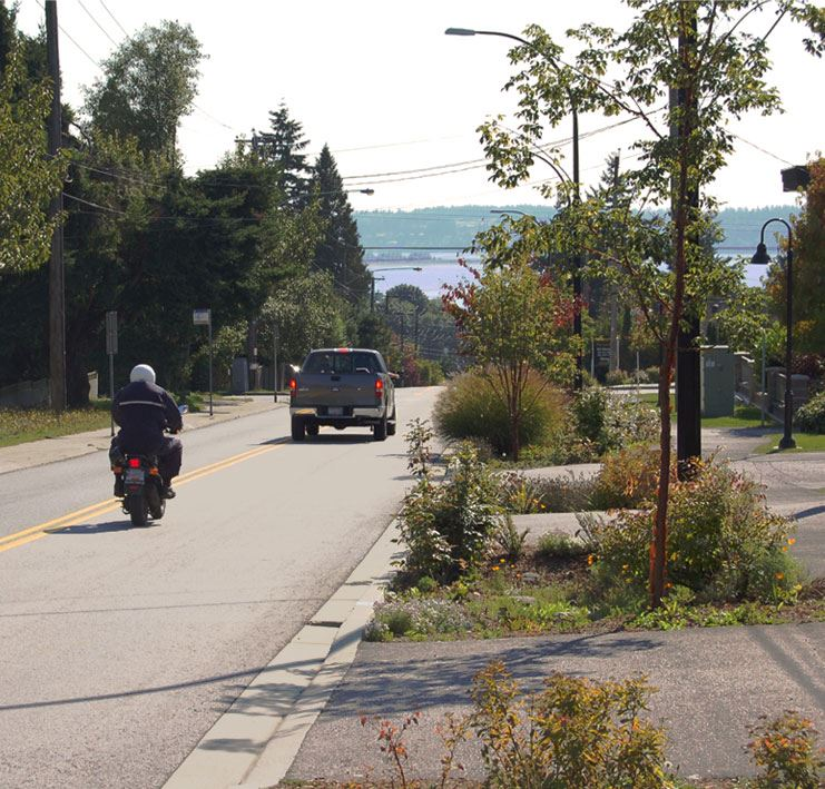 motorcycle and truck driving down hill towards waterfront - transportation survey