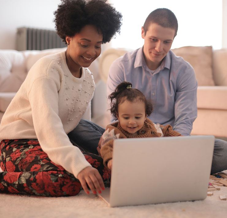 Mother, Father and Child sitting on floor with laptop